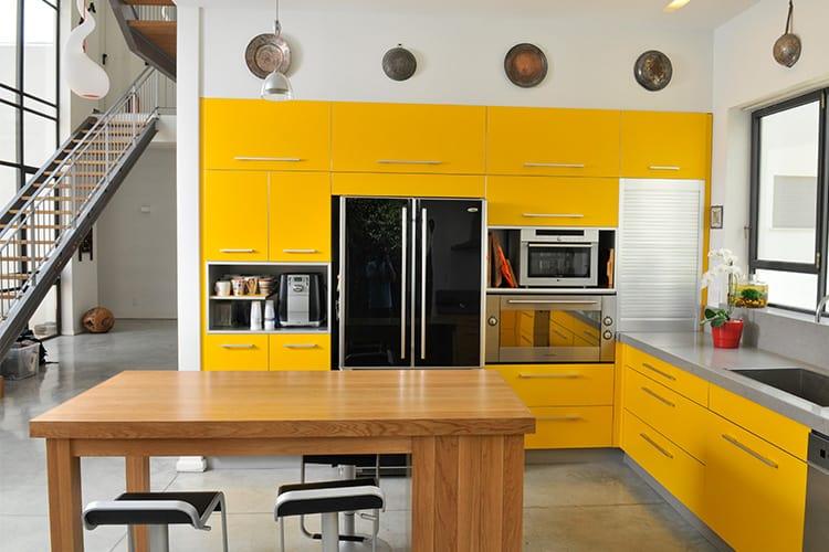 מטבח מודרני בהתאמה אישית בצבע צהוב על רצפת בטון מוחלק