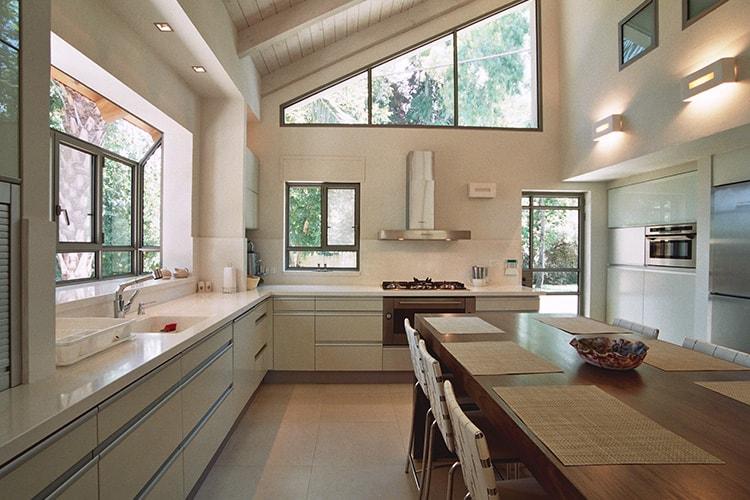 מטבח מודרני לבן בהתאמה אישית עם גימור נירוסטה עם שולחן אוכל מעץ וכסאות רצועות עור לבן