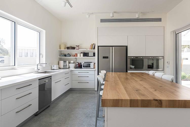 מטבח מודרני לבן בהתאמה אישית בשילוב נירוסטה ואי מטבח לבן עם משטח עץ אלון
