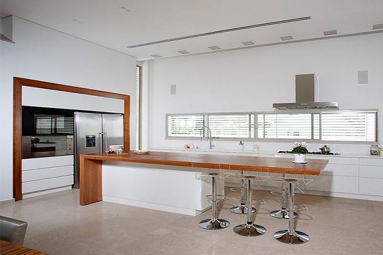מטבח מודרני לבן בהתאמה אישית עם עם אי צף מעץ מלא וכסאות בר שקופים