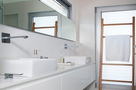 חדר רחצה בהתאמה אישית בסגנון מודרני בצבע לבן עם שני כיורים