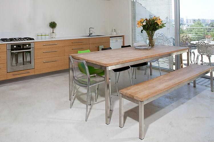 שולחן אוכל עם ספסל ישיבה בנגרות אישית וכסאות אקלטיים בתוך מטבח מודרני