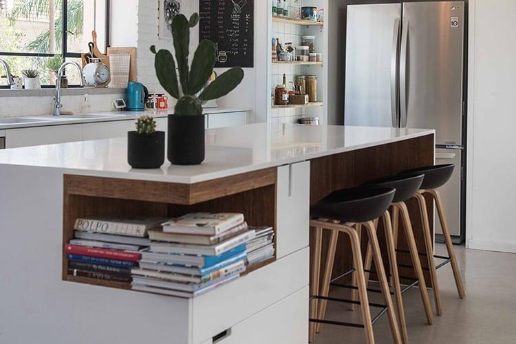 אי מטבח לבן בעיצוב מודרני בהאמה אישית עם גימורי מעץ וכסאות בר עם מושבים שחורים