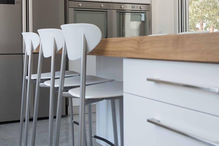 כסאות בר לבנים מול אי מטבח לבן בעיצוב מודרני בהתאמה אישית