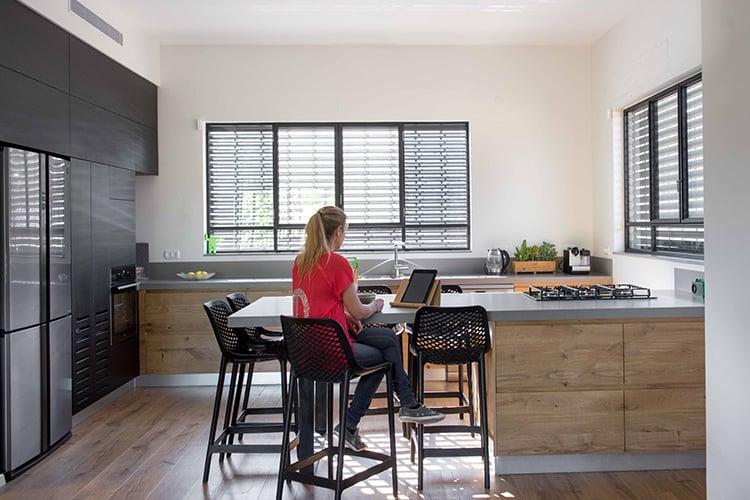 אישה יושבת ועובדת על כיסא בר במטבח מודרני חמים בהתאמה אישית