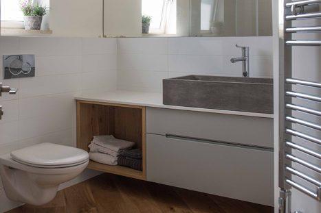 חדר רחצה בהתאמה אישית בסגנון מודרני בצבע לבן ועץ עם כיור בטון