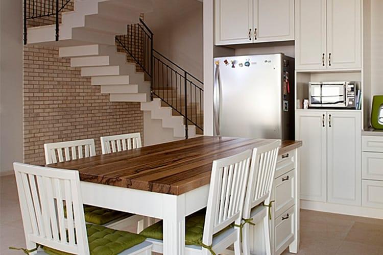 מטבח לבן בסגנון כפרי ליד קיר בריקים ומדרגות