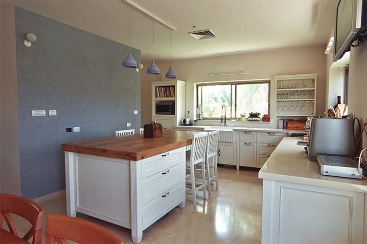 אי מטבח כפרי בצבע לבן עם מגירות אחסון ומשטח עץ מלא