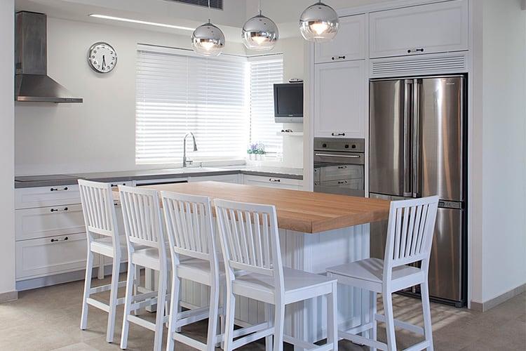 אי עם כסאות גבוהים במטבח לבן בעיצוב כפרי