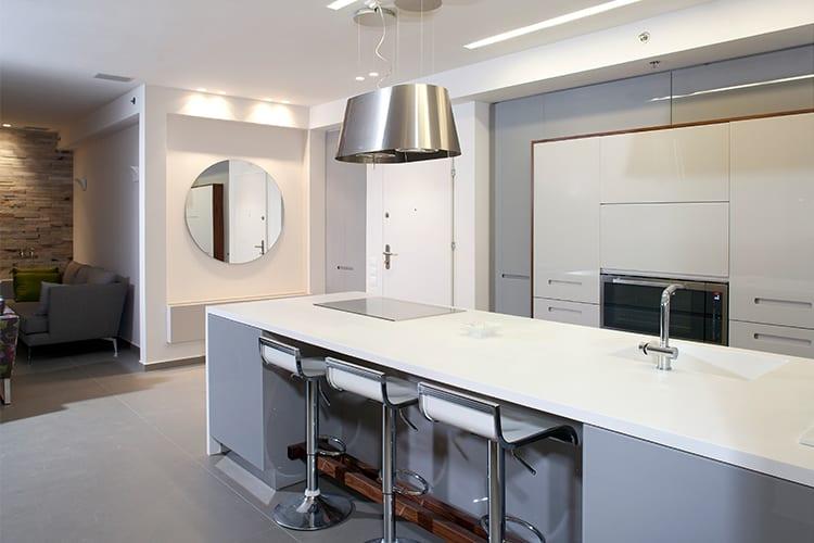 מטבח מודרני בהתאמה אישית בצבע לבן עם אי ארוך וכסאות בר