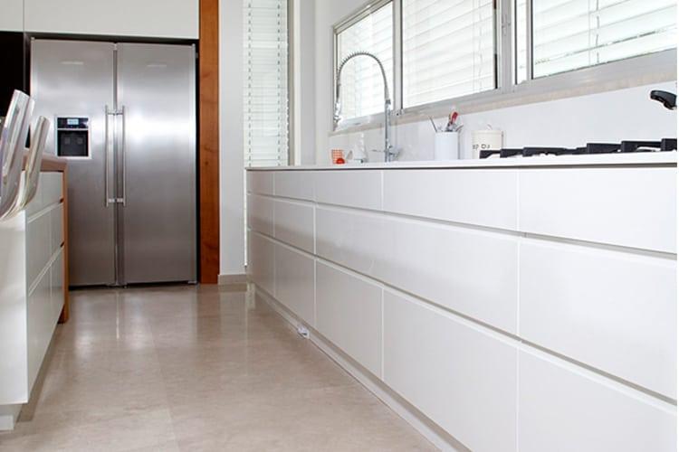 דלפק ארוך במטבח מודרני בהתאמה אישית בצבע לבן על רצפה בהירה